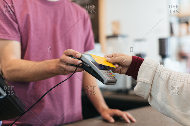 Close up of a woman using the tap to pay option while paying for coffee