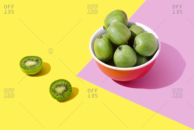 Kiwi berries in a pink bowl on a yellow and pink background