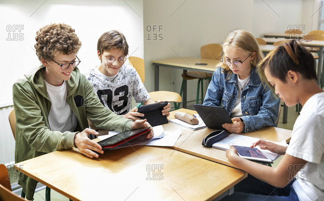 Teenagers in classroom using digital tablets