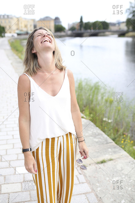 Happy woman standing at river