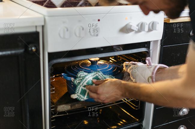 Man putting pot inside oven