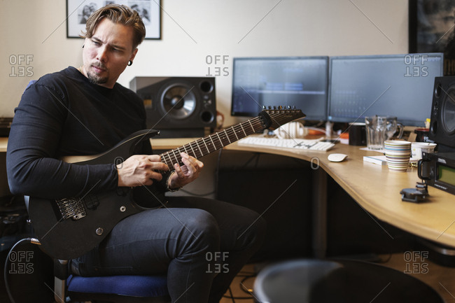 Man with electric guitar sitting at desk
