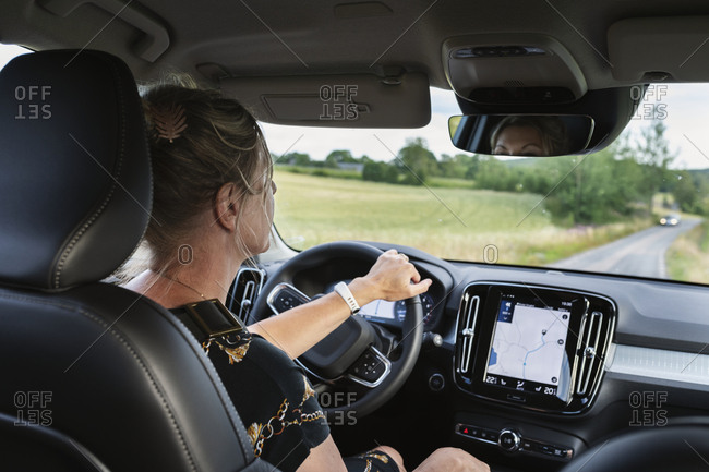Woman driving car with GPS on dashboard