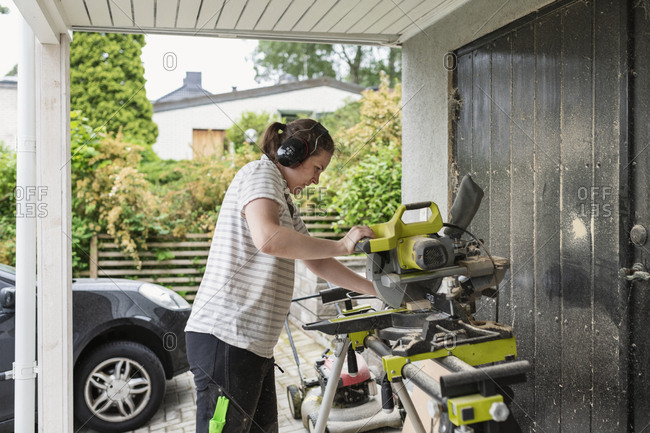 Woman using bench saw