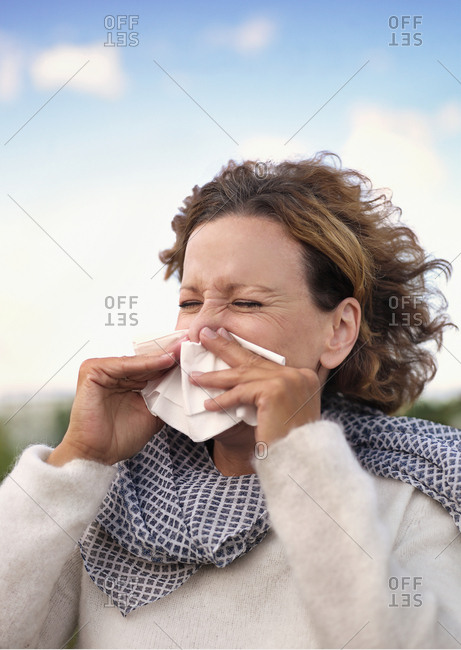 Woman with eyes closed sneezing