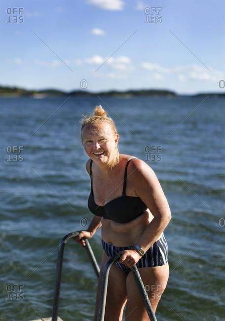 Smiling woman standing in bikini