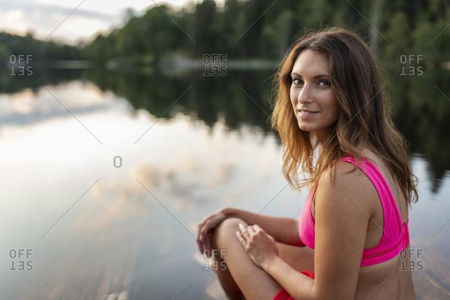 Smiling woman sitting at lake