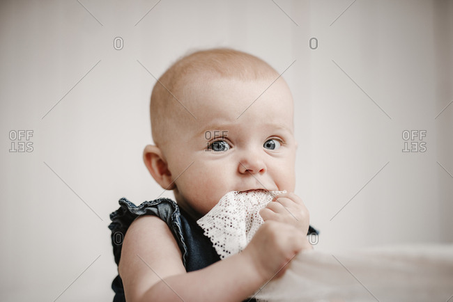 Baby girl holding material in mouth