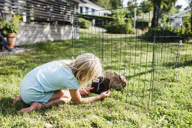 Girl taking picture of rabbit in cage