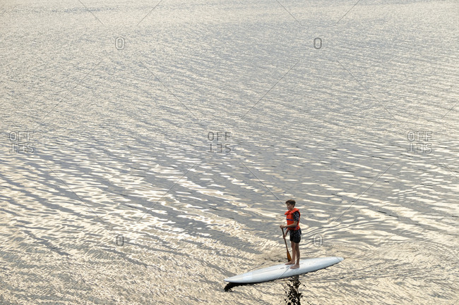 Boy standing on paddleboard