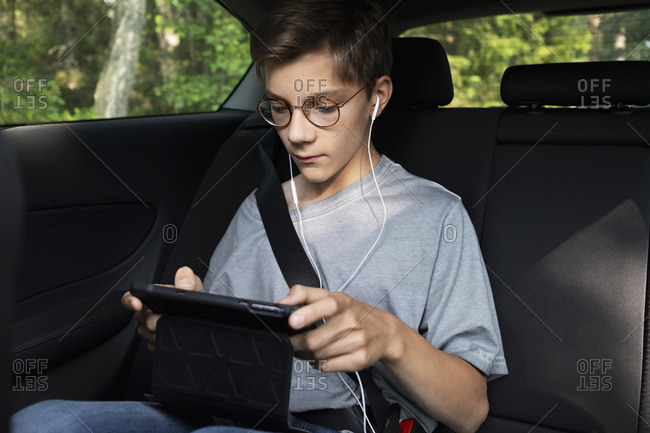 Boy using cell phone in car