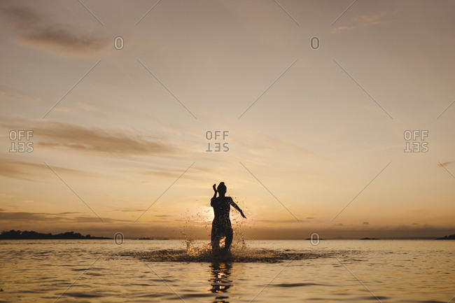 Woman bathing in sea at sunset