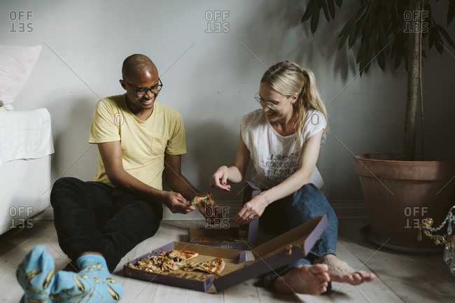 Couple sitting on floor and having pizza