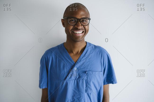 Man wearing scrubs looking at camera