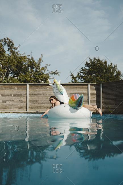 Woman on inflatable unicorn in swimming-pool
