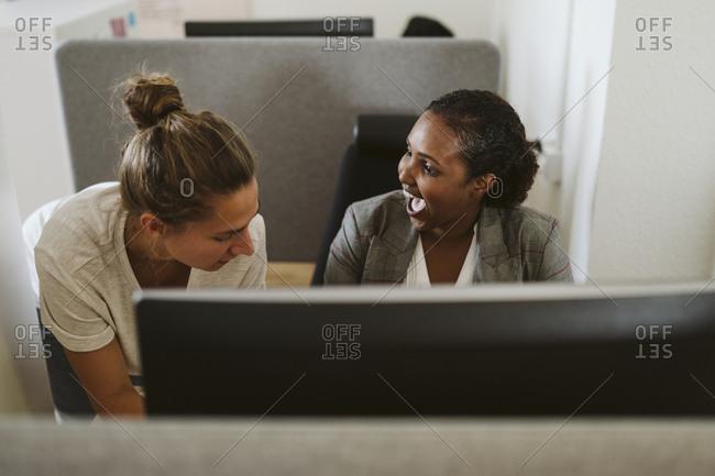 Smiling women talking in office