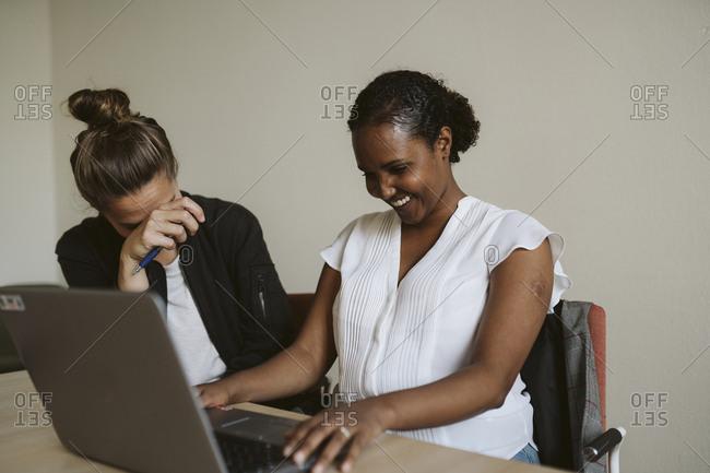 Smiling women using laptop