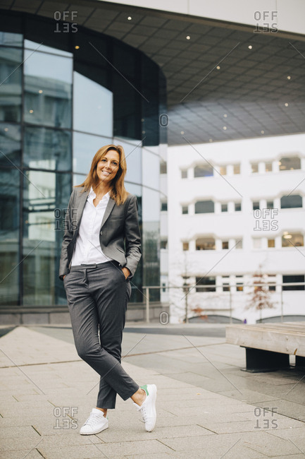 Full length of confident smiling businesswoman standing against glass building
