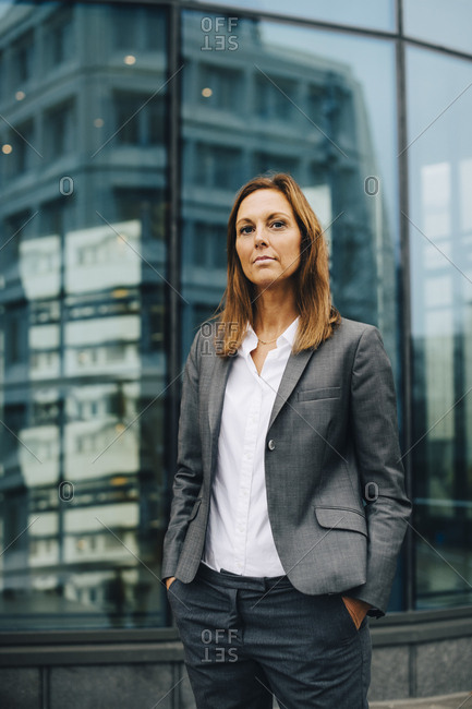 Portrait of confident businesswoman standing against reflection on glass building