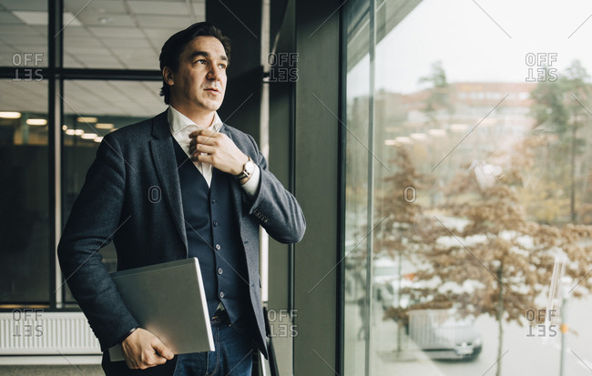 Businessman adjusting collar while standing with laptop by window in office