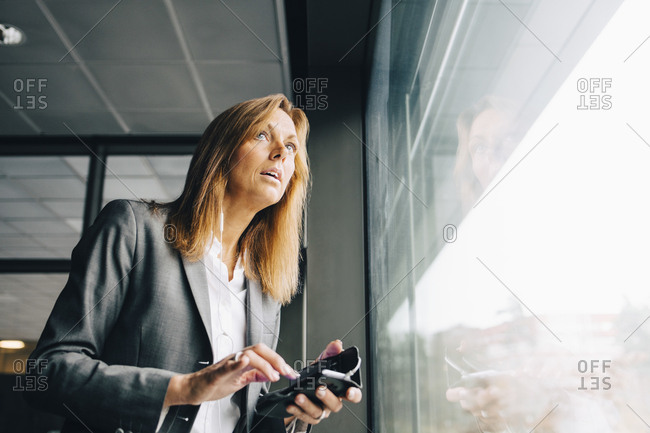 Thoughtful businesswoman with mobile phone looking through window in office