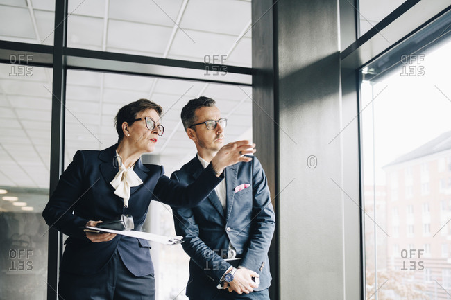 Senior businesswoman looking away while discussing with colleague in office