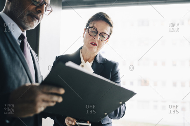 Senior professional discussing strategy with colleague at workplace