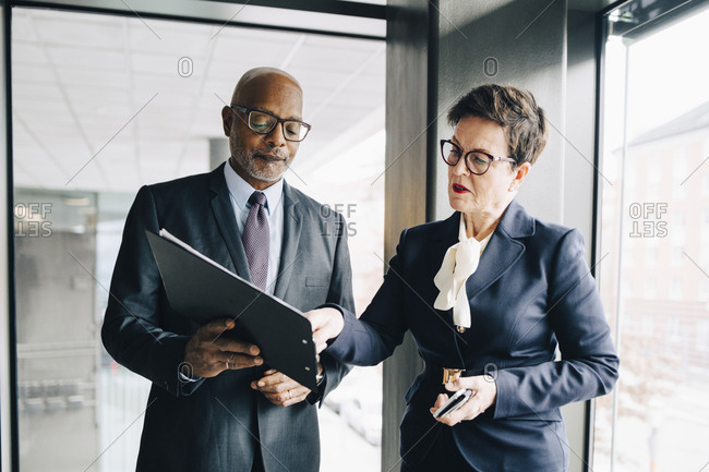 Senior businesswoman explaining strategy to colleague in conference room at office