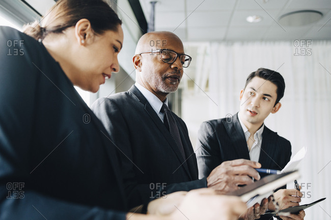 Senior businessman discussing ideas with colleagues in conference room at office
