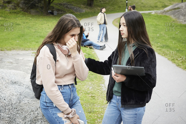 Teenage girl looking at female friend crying while sitting on rock at park