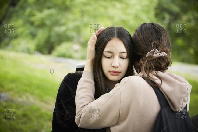 Teenage girl consoling female friend