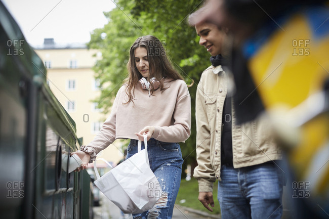 Smiling man looking at female friends throwing waste in garbage bin