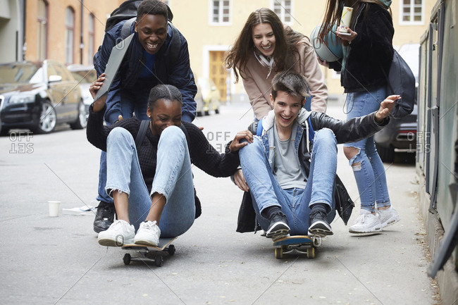 Cheerful friends pushing teenagers sitting on skateboard