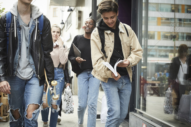 Young man holding book while walking with teenage friends in city