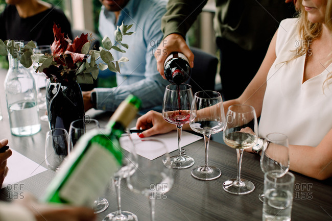 Cropped image of businessman pouring red wine in glass at convention center