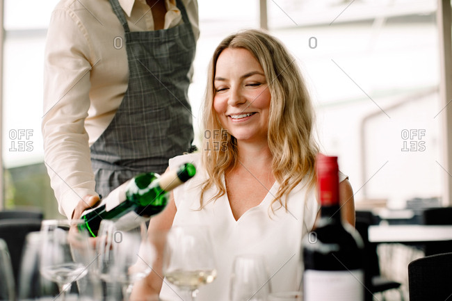 Businessman serving wine to smiling female colleague at convention center