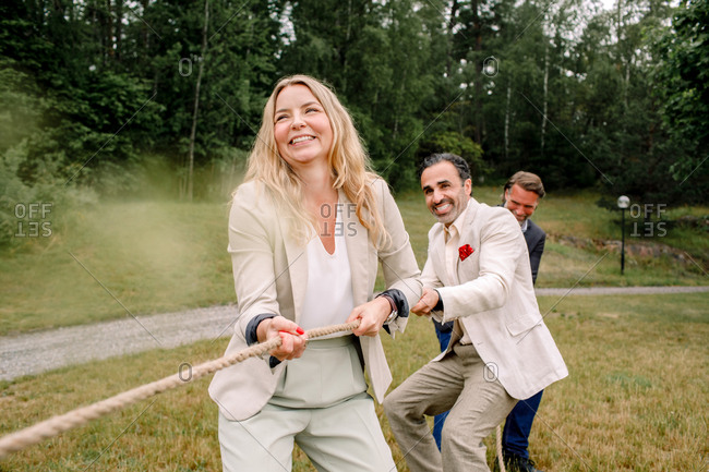 Smiling male and female colleagues pulling rope while playing tug-of-war in lawn