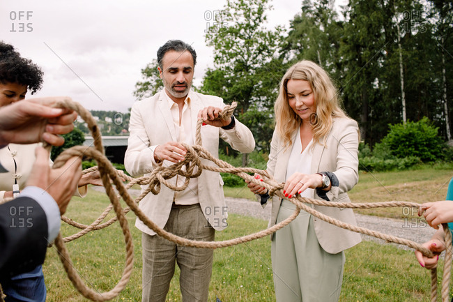 Male and female business professionals holding tangled rope while standing in lawn