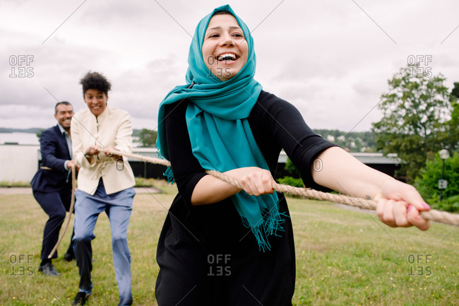 Smiling multi-ethnic male and female colleagues pulling rope while playing tug-of-war in lawn