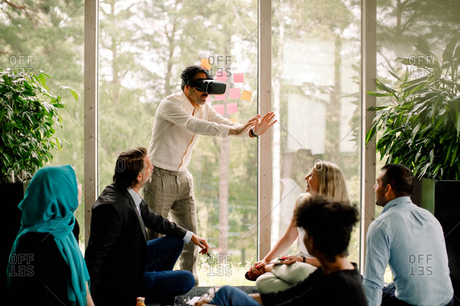 Businessman wearing virtual reality simulator during conference with colleagues at convention center
