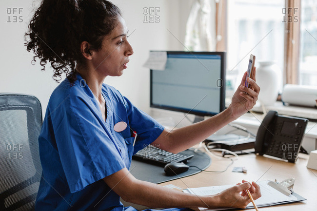 Female healthcare worker talking on video conference through mobile phone in doctor's office