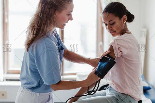 Mature nurse checking patient's blood pressure in examination room at clinic