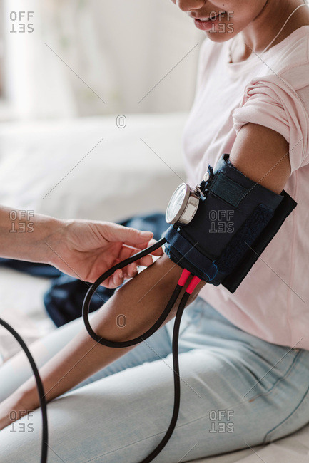 Cropped hand of nurse checking patient's blood pressure in medical room