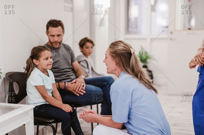 Female pediatrician talking with girl sitting by family in hospital corridor