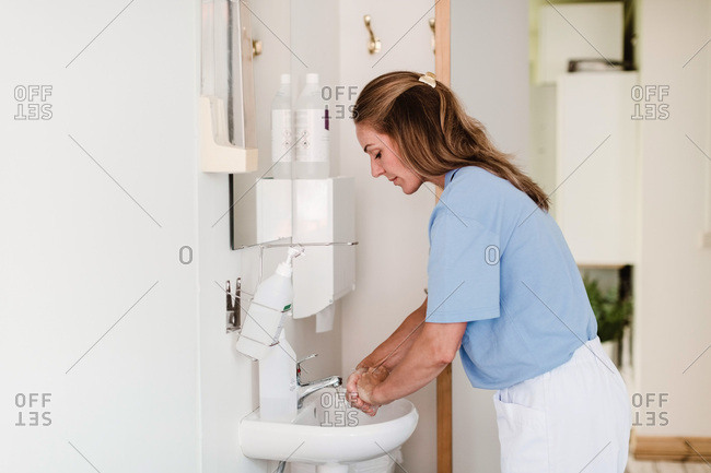Side view of female doctor washing hands at sink in medical examination room