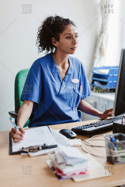Female nurse writing report while using computer in hospital