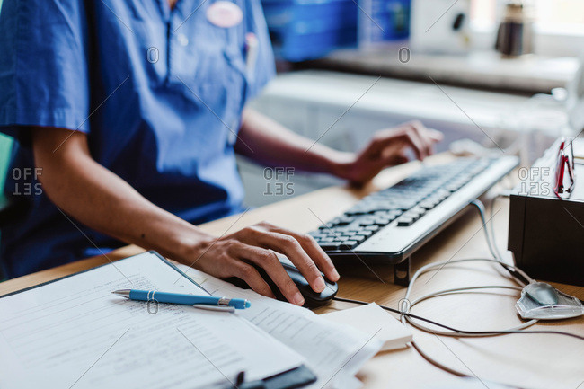 Midsection of nurse using computer at desk in hospital