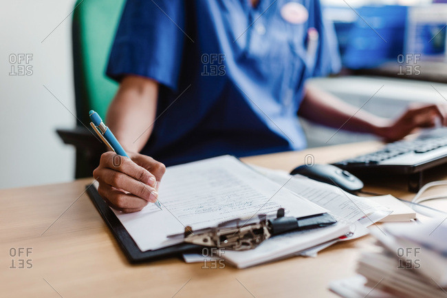 Midsection of nurse writing medical report while sitting at desk in clinic