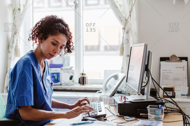 Side view of female nurse making medical report in computer at clinic
