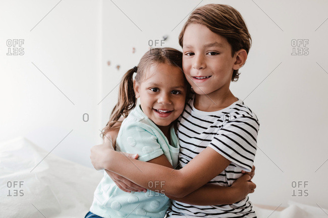 Portrait of smiling brother and sister embracing while sitting in medical examination room